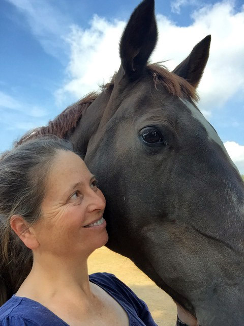 Kate smiling with a black horse